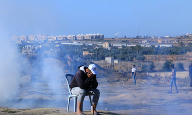 A man sits outside on a plastic chair as smoke billows behind him.