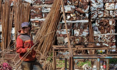 A man carries steel bars with bare hands in a yard filled with scrap metal.
