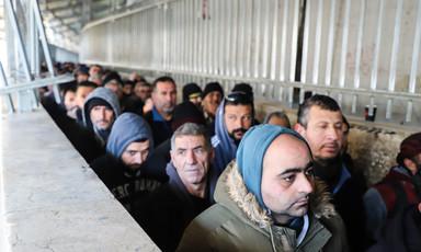 Men queue in a concrete walkway