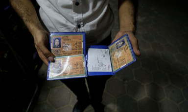 A man holds temporary ID cards that are void for travel.