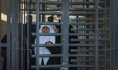 A woman pushes at the metal bars of a caged turnstile