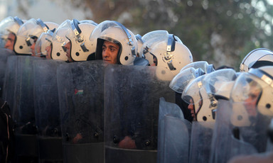 Police officers wearing helmets hold riot shields