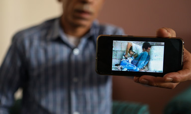 A man holds out a mobile phone showing a still from grainy video footage