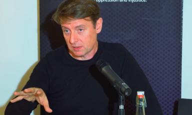 A man talks behind a microphone