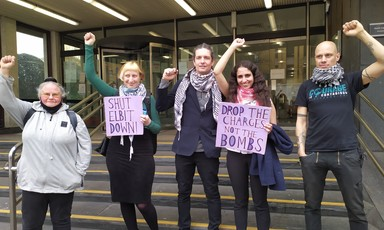 Five people raising fists and holding two signs