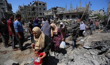 Women walk amid rubble