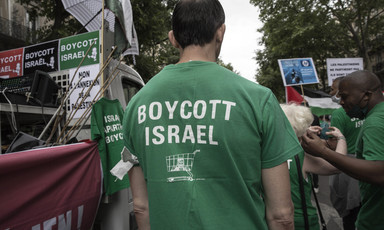 Man in crowd wears T-shirt reading Boycott Israel with icon of a shopping cart
