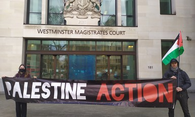 "Two protesters hold a ""Palestine Action"" banner outside a court"