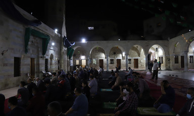 Men pray in the dark in an outdoor mosque courtyard