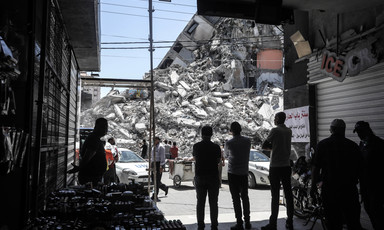 Silhouetted people stand in front of giant mound of rubble from a destroyed building
