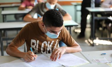 Boy wearing mask writes on paper