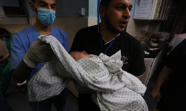 Man holds a baby wrapped in a sheet