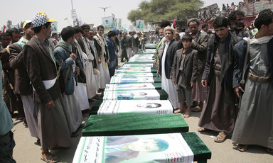 Men stand on either side of a row of coffins draped with banners showing portraits of the slain children