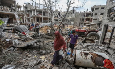 Woman and boy walk through street filled with rubble and lined by bombed-out apartment blocs