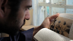 Man looks at Arabic-language book and vintage photograph of armed men