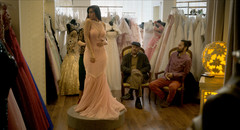 Woman wearing beaded gown stands on pedestal as two men sitting on chairs look on in bridal dress shop