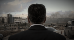 View of the back of a man's head in front of the Ramallah cityscape