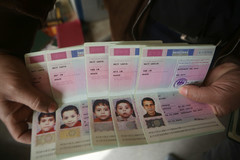 A pair of hands holds five passports opened to page showing photos