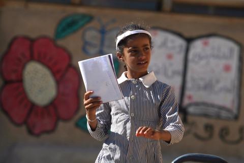 Girl in school uniform holds book