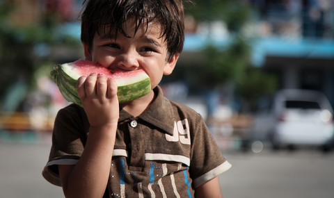A smiling young boy eats a slice of watermelon