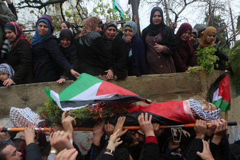 Mourning women look down on youth's body as he is carried in funeral procession