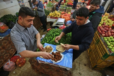 Two men stand at table making falafel sandwiches in middle of produce shop