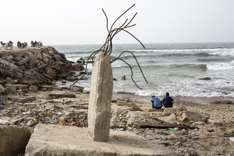 Photo shows the backs of two youths sitting on a beach strewn with litter and rubble