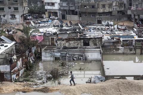 Wide view of boy walking in front of flooded neighborhood of shanty dwellings
