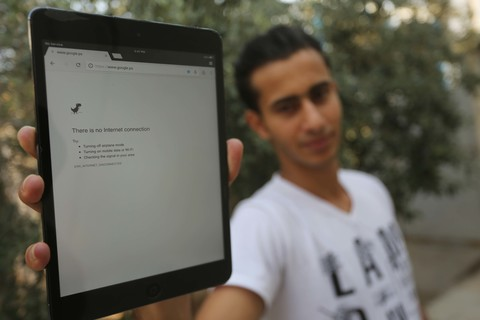 Young man holds up electronic tablet showing an Internet browser error stating, There is no Internet connection