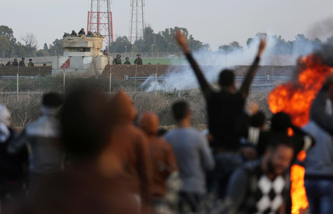 Israeli soldiers in watchtower and along fence look on in background as Palestinian youths with backs to their camera are seen in foreground