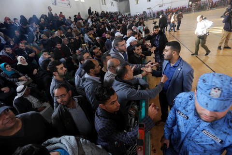 Dozens of people sit in the bleachers of a gymnasium used as a waiting area