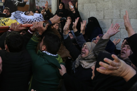 Photo shows crying women waving their hands at shrouded body of young man being carried on stretcher