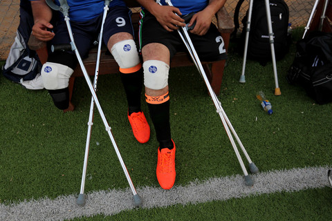 Photo shows legs and crutches of men in football uniform sitting on a bench at a football pitch