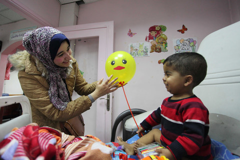 A young woman greets a child holding a balloon as he sits up on his hospital bed.