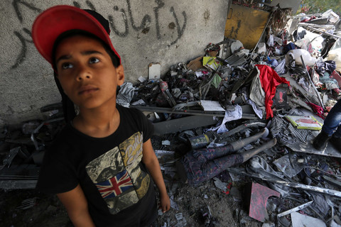 Boy stands in front of room filled with debris