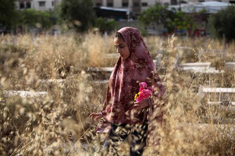 Woman wearing headscarf holds flowers in a wheat field