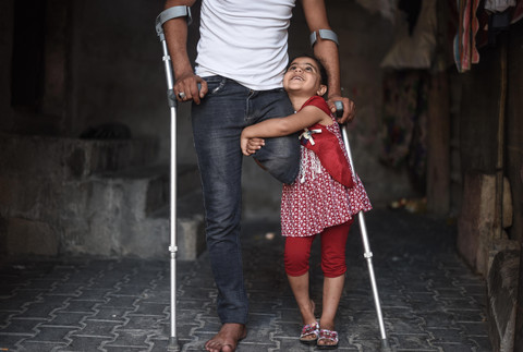 Girl hugs man using crutches seen from chest down