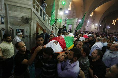 Men carry two dead bodies covered by shrouds and flags.