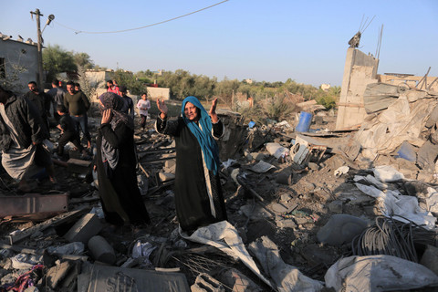 Woman throws her hands in the air while standing on rubble