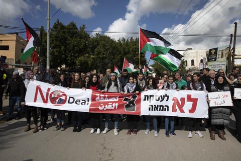 Demonstrators holding large banner, flags