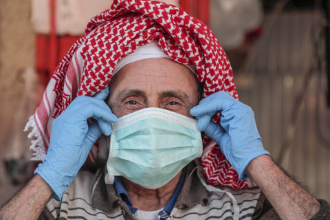 Man wearing headscarf adjusts protective mask on his face