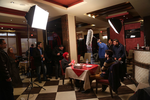 Film crew members stand around male and female actors sitting on opposite sides of a restaurant table