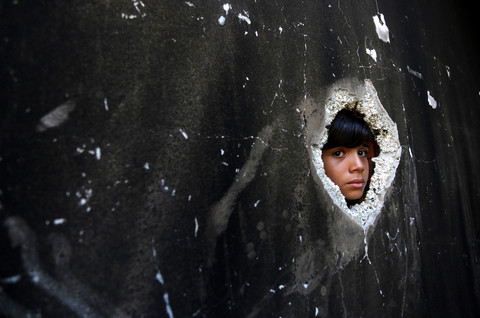 The face of a boy peers through a hole in the wall