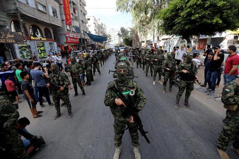 A parade of masked men, carrying guns
