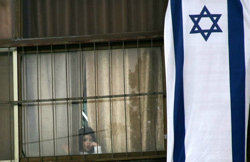 Small girl peers out of window covered with giant Israeli flag