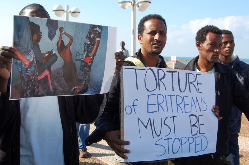 Men hold signs protesting the torture of Eritreans