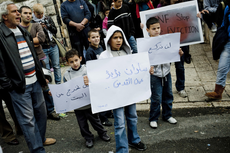 Children hold signs protesting evictions in Silwan