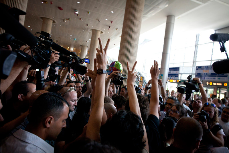 "Activists give the ""victory"" hand gesture as they are surrounded by media"