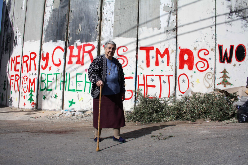 "Woman walks in front of wall reading ""merry Christmas from Bethlehem Ghetto"""