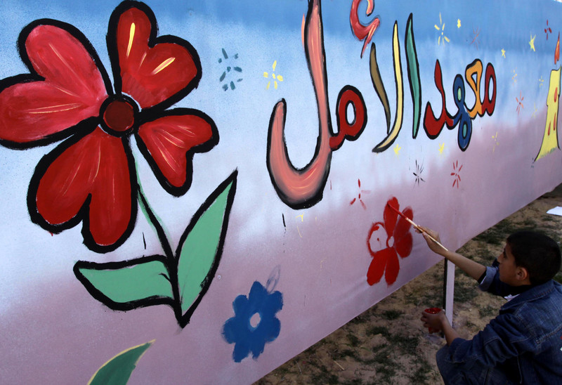 Boy paints mural of flowers on orphanage wall
